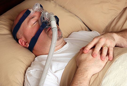 Man Wearing CPAP Device
